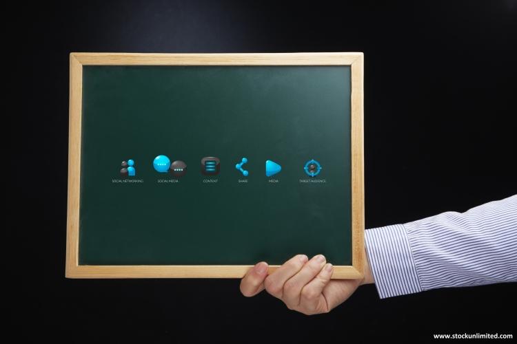 Una mano sujeta una pizarra con iconos informáticos