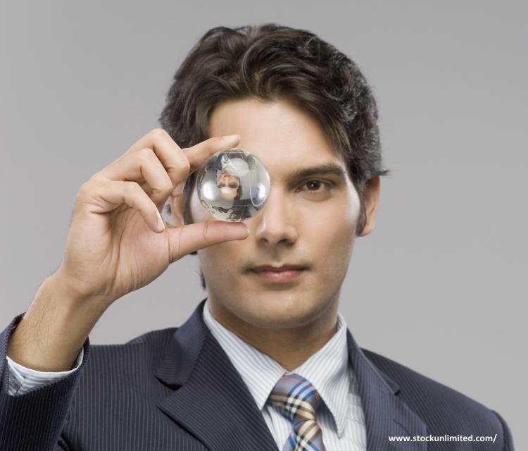 Un ejecutivo mirando una bola de cristal que tiene entre sus dedos.